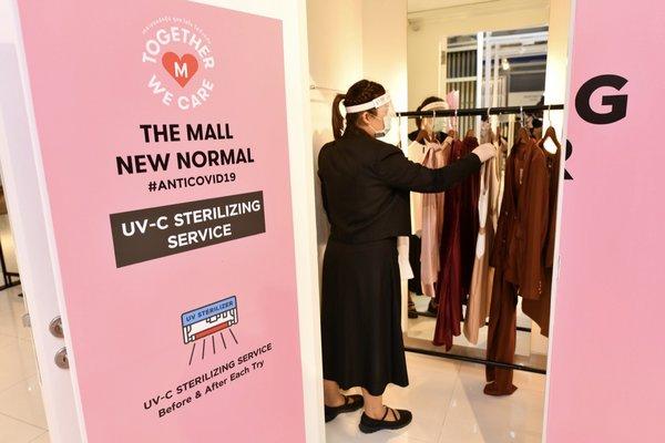商場工作人員在UV- C消毒間準備對衣物進行消毒